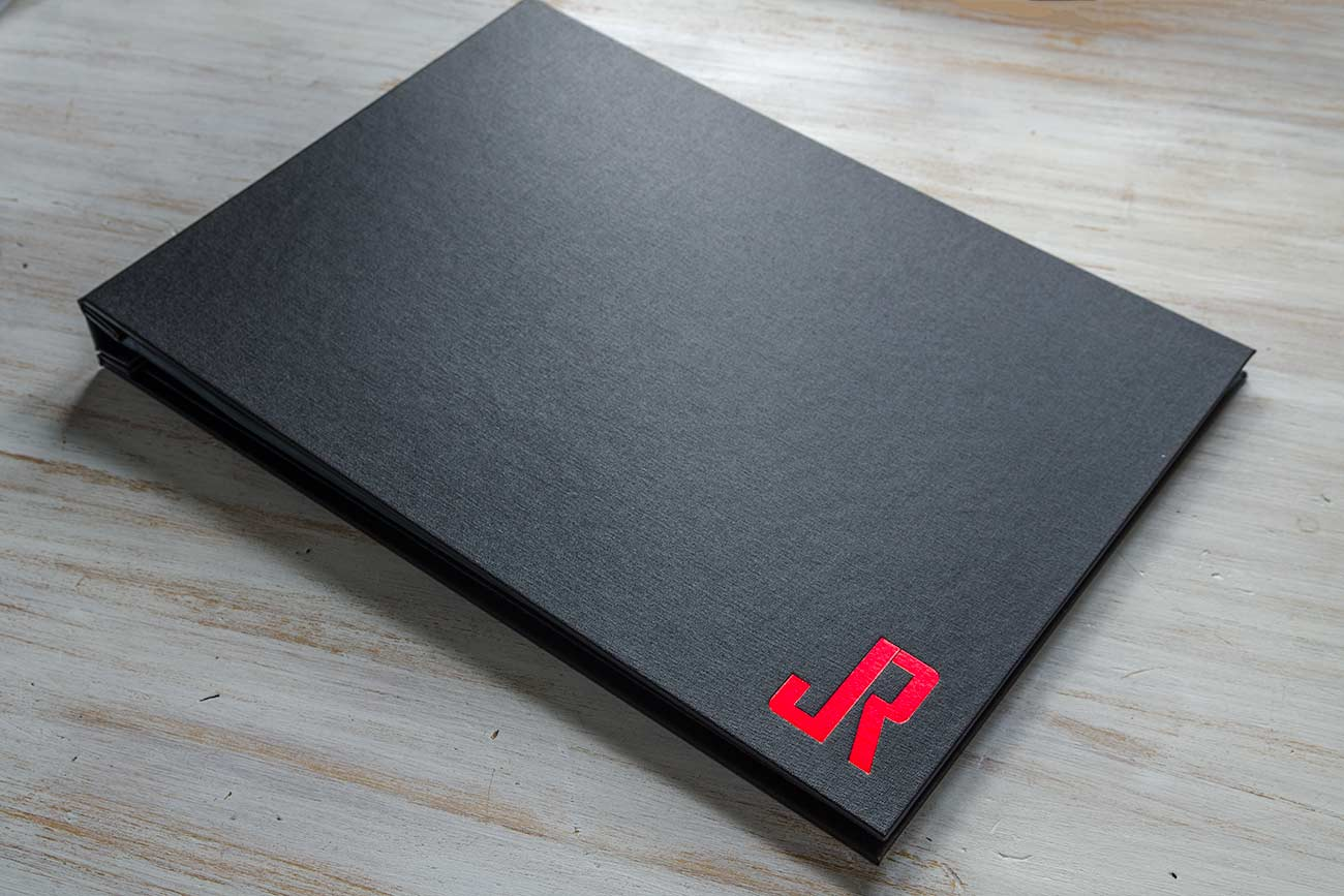 Custom and personalized portfolio book in black buckram and metallic red foiling