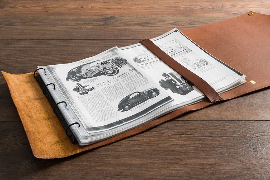 rolled leather scroll with ring binder mechanisms to keep long lengths of A3 paper and posters for classic car