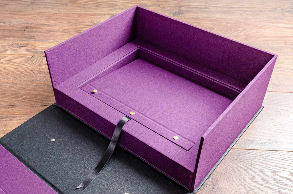 Hidden compartment in the clamshell box reveals a binder where photographs and documents for the car can be kept