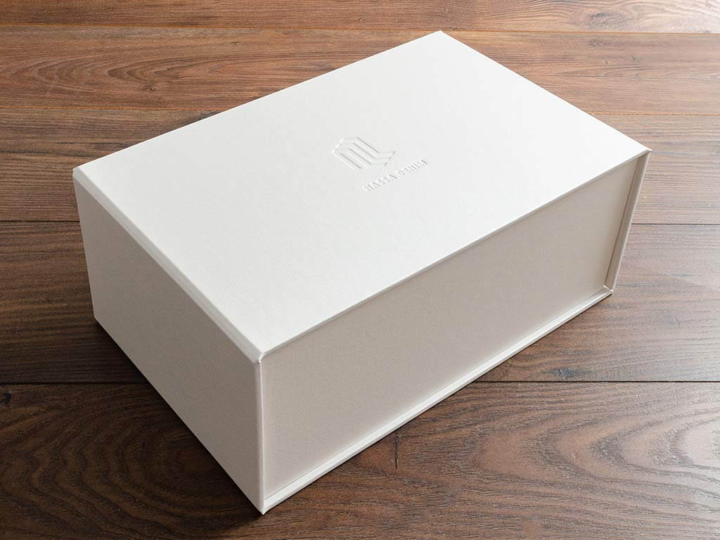 Custom sized swatch box in White buckram cloth and a blind debossed logo