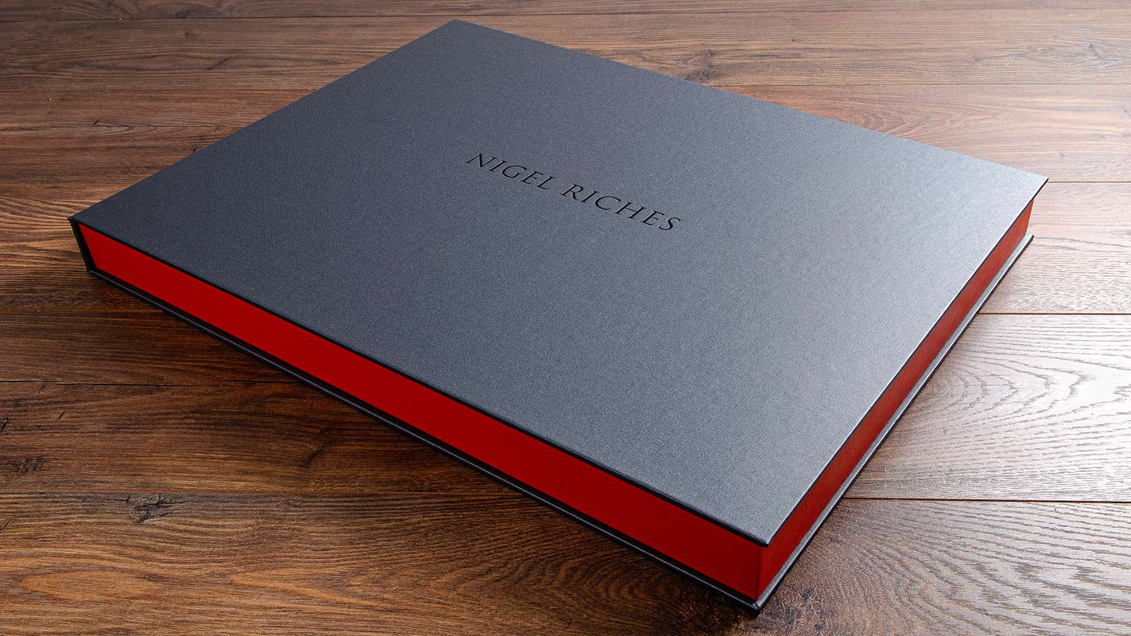 photographers portfolio box with embossed logo in black foil and grey buckram outer cover and a orange tray.