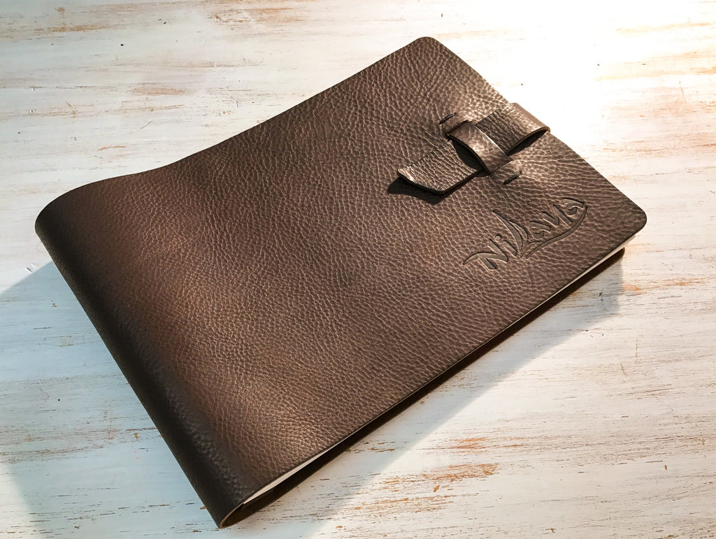 Custom made leather book for yacht SY Nilaya with blind debossed personalisation on the cover