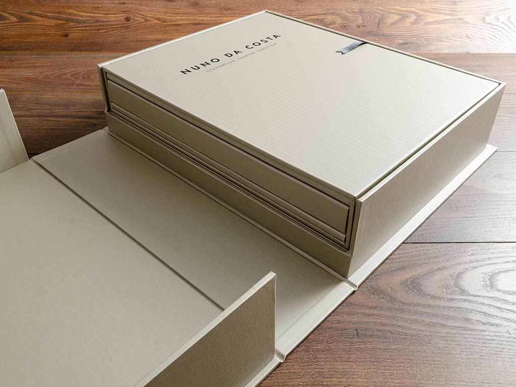 Illustrators portfolio book housed within a slipcase sitting on a shelf in a clamshell box