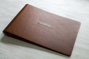 brown leather portfolio book with embossed logo on cover