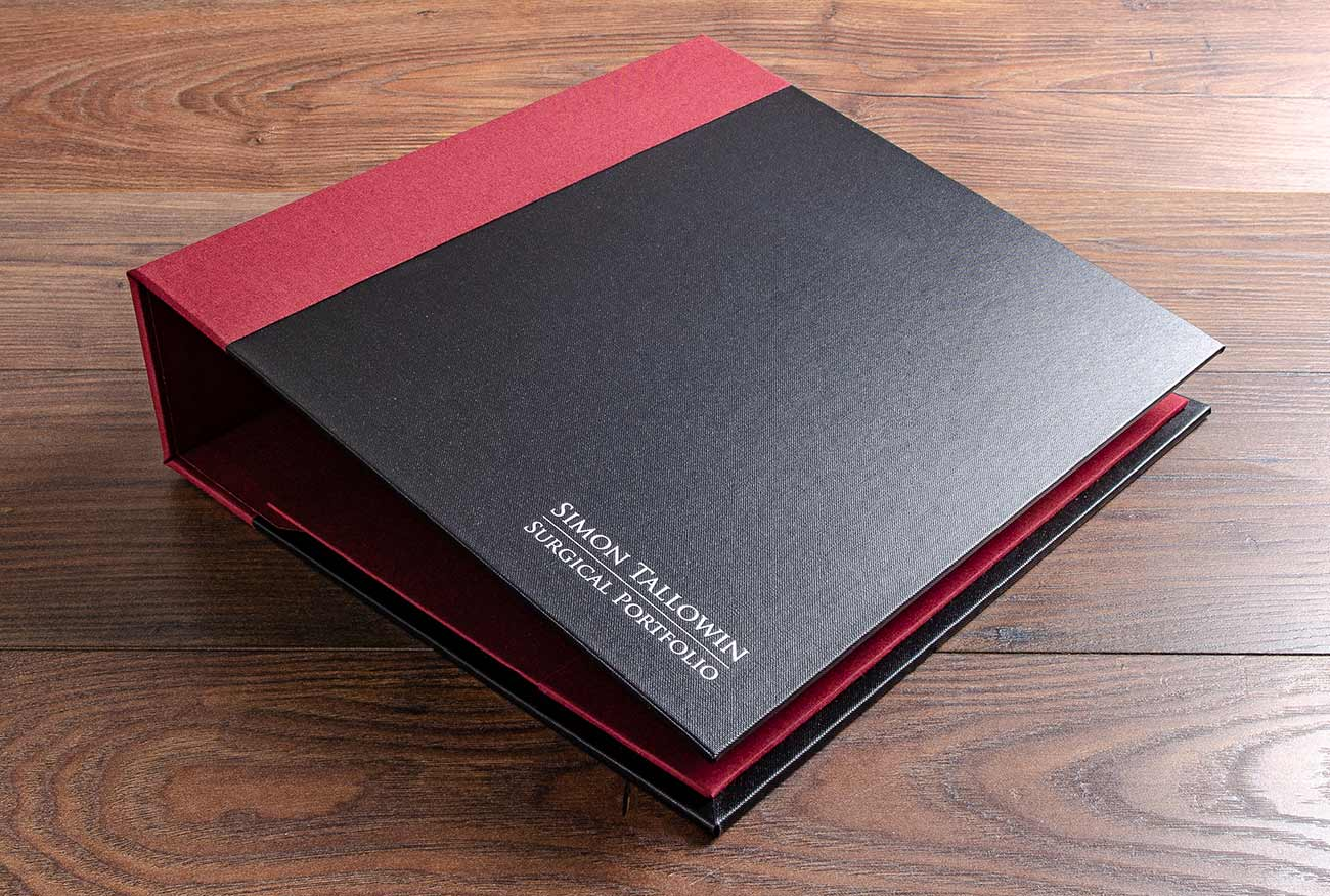 Surgical evidence portfolio in charcoal black buckram and a vistula red spine cover with silver foil personalisation
