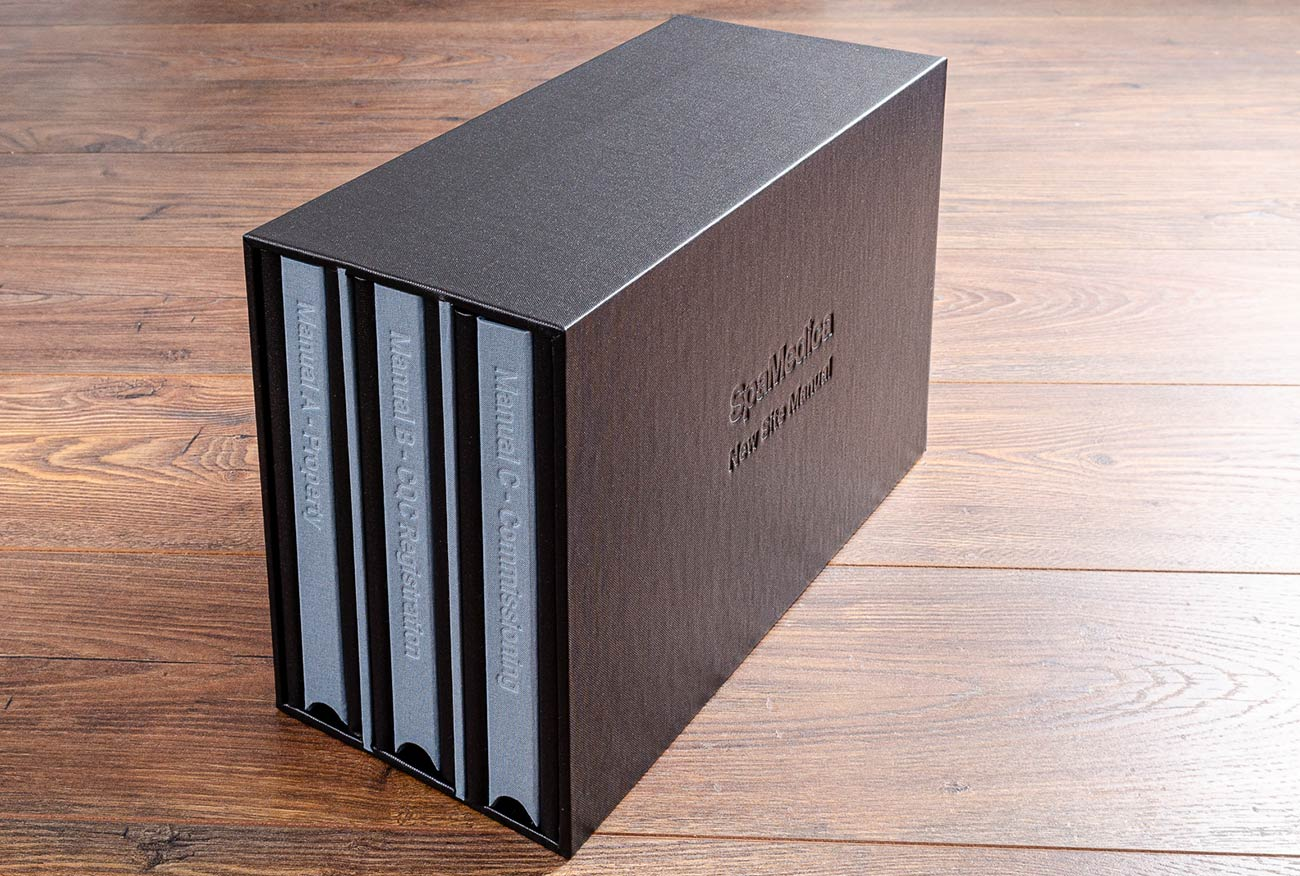 A slipcase holding three A3 portfolios in charcoal buckram with a blind embossed cover