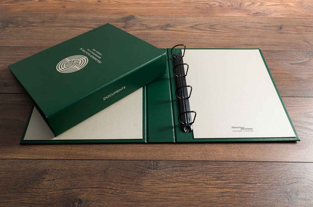 A set of ring binders in Bottle green buckram and Beige buckram with personalised cover and spine in metallic foil