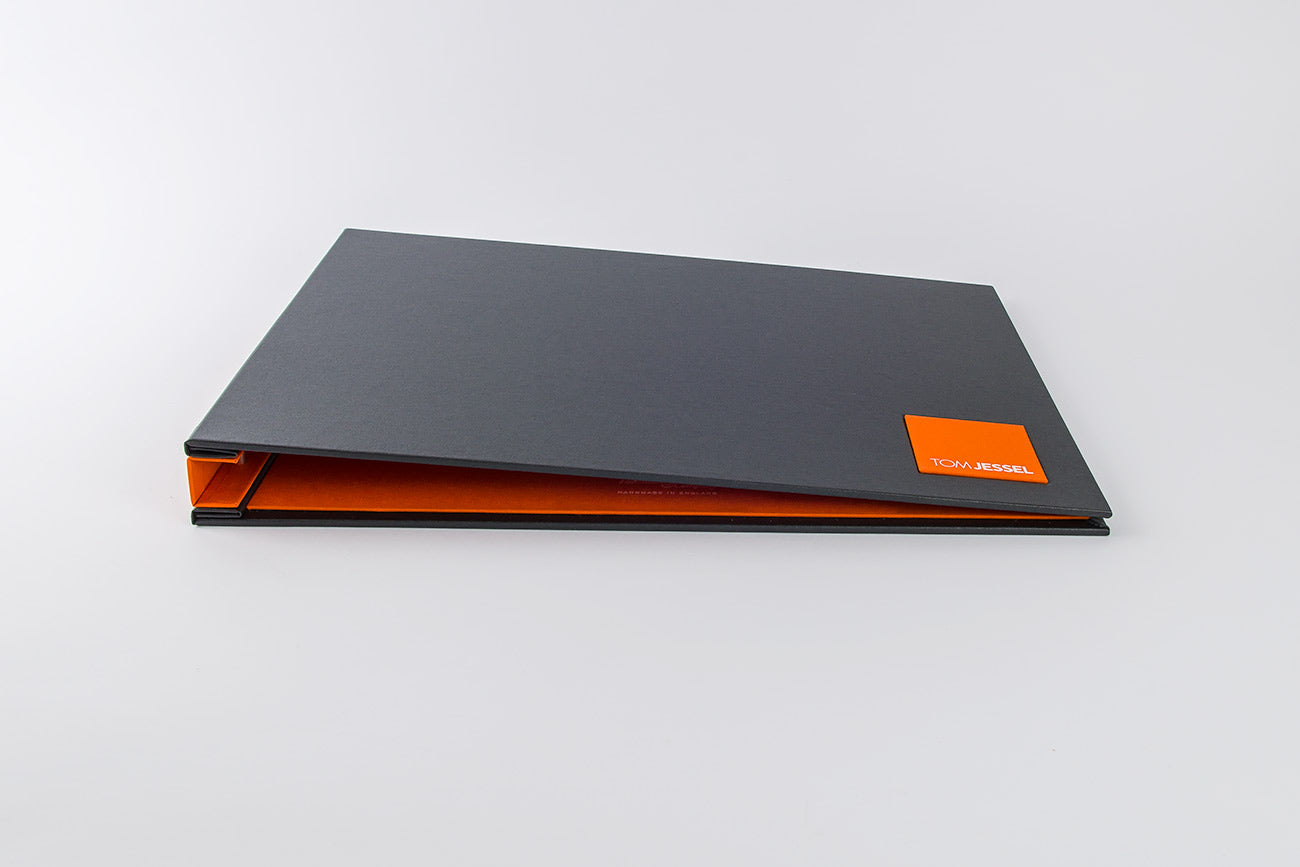 Custom graphic designers hidden screw post portfolio - Charcoal buckram outer cover. Solo orange name plaque, inner cover and spine cover