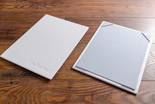 Luxury leather menu board in white leather and blue grey material boards with A5 page holders in the corner