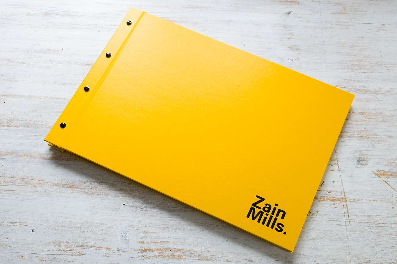 A3 Landscape exposed screw post presentation book for designer photographer in yellow buckram and black book cloth with black foil personalisation and screw posts