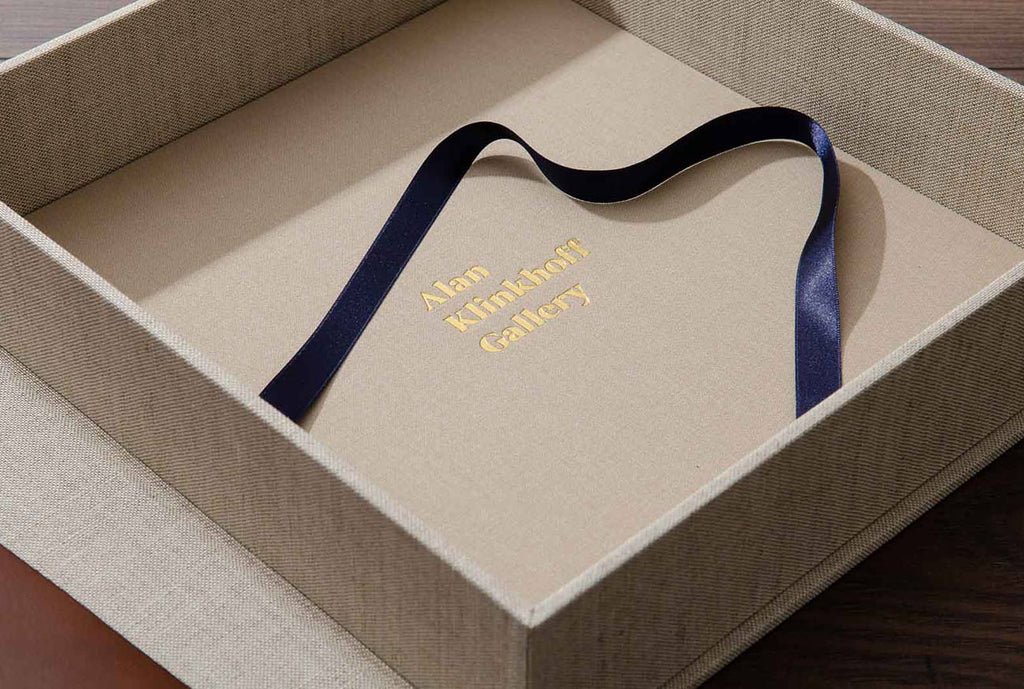 Interior of clamshell box with blue pull ribbon and gold foil personalisation
