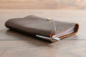 Leather Notebook Cover Closed Holding Three Field Note Book and Ball Point Pen