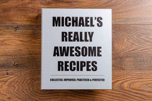 Personalised recipe binder in platinum buckram bookcloth with the words Really Awesome Recipes Collected, Improved, Practiced and Perfected printed on the cover