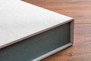 The inner tray on this clamshell box is covered in Pampas Green Windsor book cloth and the outer cover is in a Medium Linen book cloth. While beautiful, book cloth is not water resistant so we recommend buckram as an outer cover