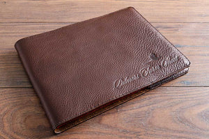 Leather book cover jacket in 2.5mm dark brown leather with blind debossed personalised logo in the bottom right hand corner