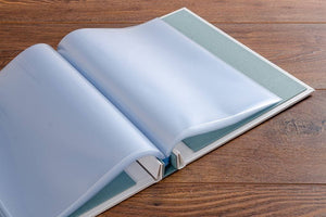 The custom screw post binder holds the page protectors firmly at the edge so that the pages turn like a bound book