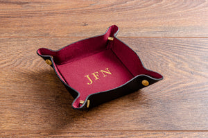 Personalised leather valet tray for coins and keys, with red fabric lining and gold foil embossing. 80mm x 80mm