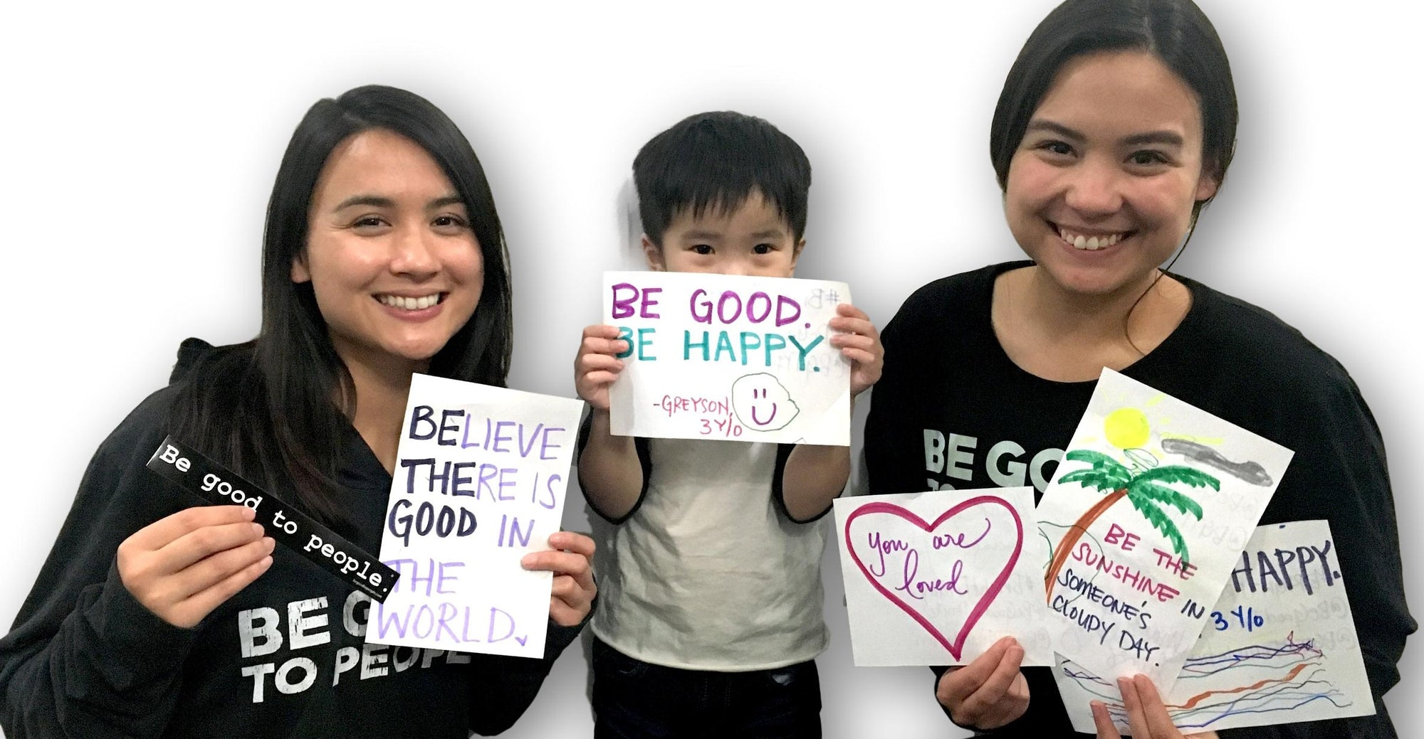Two women and a little boy, all smiling and wearing Be Good to People t-shirts and holding homemade kindness signs before they go put them on people's car windshields for Random Acts of Kindness Week