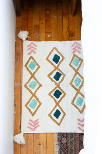 Small accent rug with pink, teal and mustard designs and pom poms