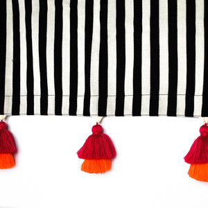black and white striped throw with pink and orange tassel