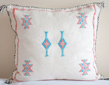 Load image into Gallery viewer, white Moroccan pillows with a Moroccan motif in the center and accent colors blue, red and black with tassels at four ends