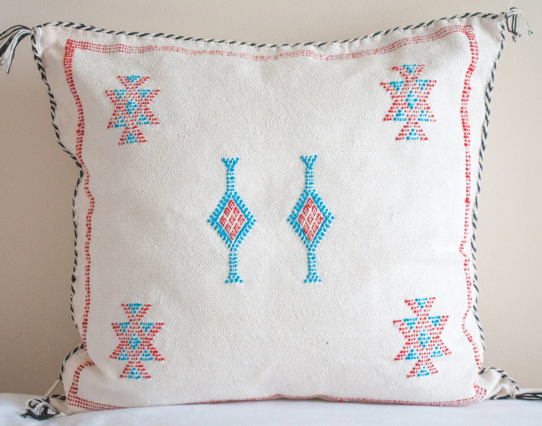 white Moroccan pillows with a Moroccan motif in the center and accent colors blue, red and black with tassels at four ends