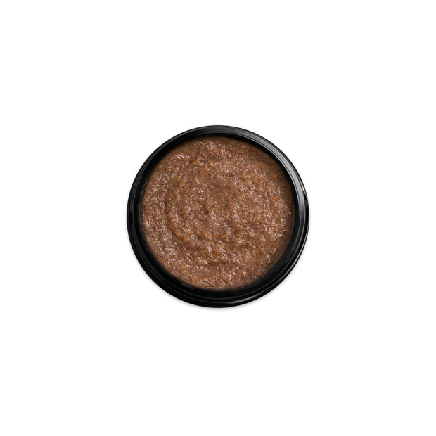 (Product image): Open 1.7oz jar of Assassin deep exfoliating scrub. Product inside is brown with a sandy texture.