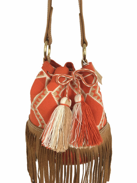Close up image of Wayuu bucket bag purse with brown leather strap and fringe; bag is orange base with white and light brown detail