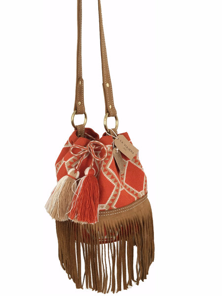 Side angle image of Wayuu bucket bag purse with brown leather strap and fringe; bag is orange base with white and light brown detail