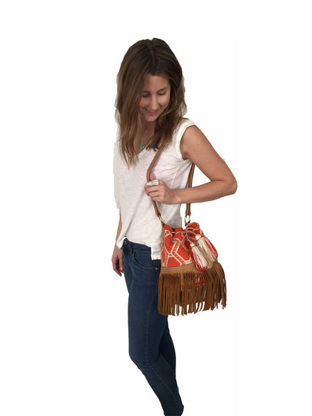 On body image of Wayuu bucket bag purse with brown leather strap and fringe; bag is orange base with white and light brown detail