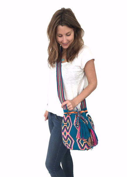 On body image of Wayuu mochila purse, drawstring crossbody bag with tassels and cloth strap; blue base with bright pink, chocolate brown, orange, tan design