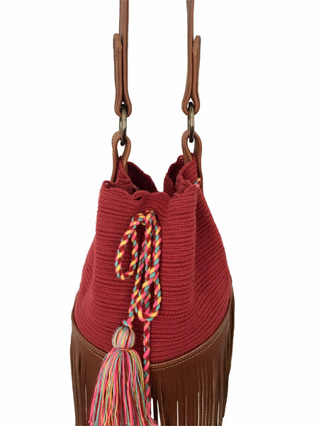 Close up image of Wayuu bucket bag purse with brown leather strap and fringe; bag is solid raspberry red with colorful tassels