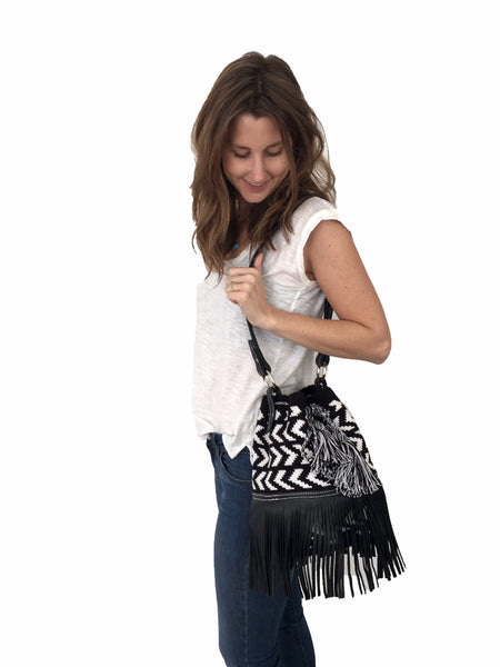On body image of Wayuu mochila purse with black leather strap and fringe; bag is black base with white arrowhead pattern