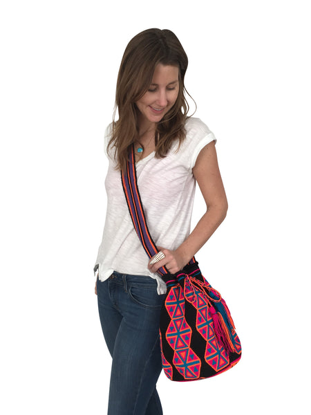 On body image of Wayuu mochila purse, drawstring crossbody bag with tassels - base color black with pink, orange and blue design