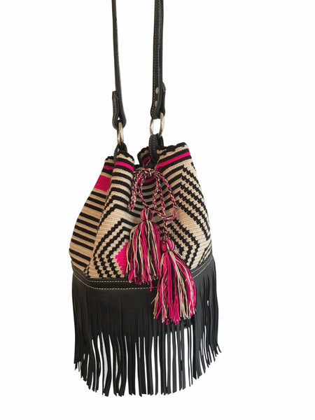 Front angle image of Wayuu mochila bag purse with black leather; bag is tan base with black stripes and bright pink detail