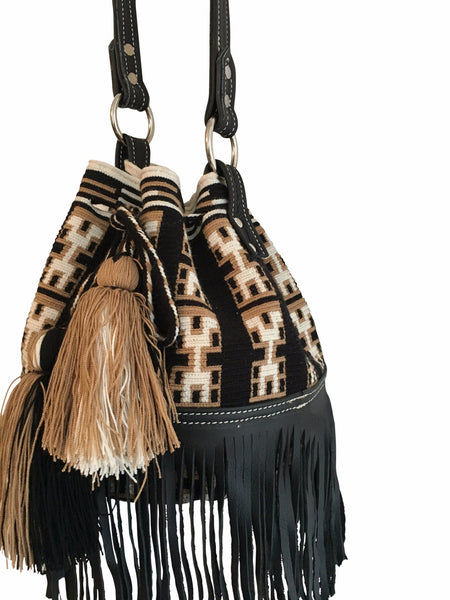 Close up image of Wayuu mochila purse with black leather strap and fringe; bag is black with tan and white detail