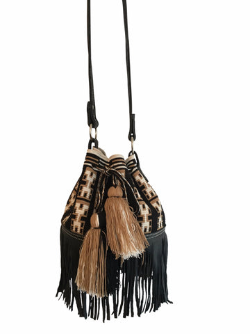Image of Wayuu mochila purse with black leather strap and fringe; bag is black with tan and white detail