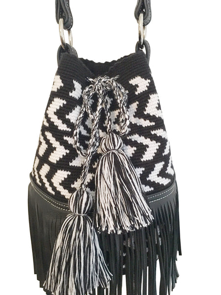 Close up image of Wayuu mochila purse with black leather strap and fringe; bag is black base with white arrowhead pattern
