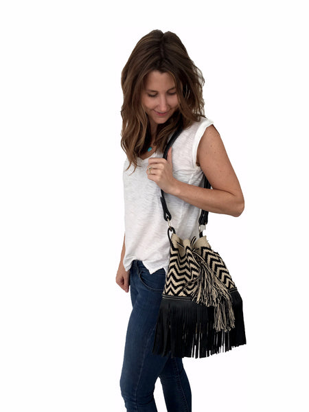On body image of Wayuu mochila purse with black leather strap and fringe; bag is tan with black zigzags