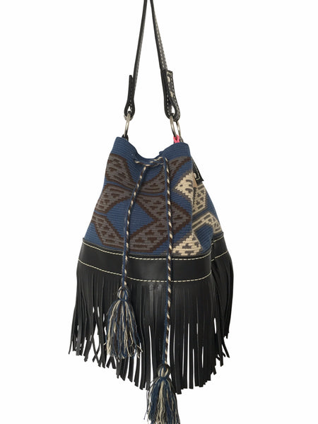 Image of Wayuu mochila purse with black leather strap and fringe; bag is navy with black and tan detail