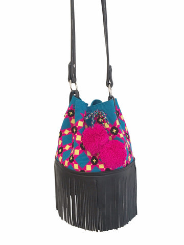 Image of one strand Wayuu purse with black leather strap and fringe; bag is blue with pink, yellow black pattern and a drawstring with two pink pompoms
