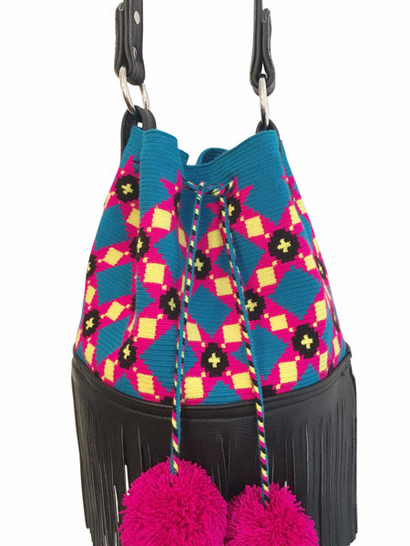 Close up image of Wayuu purse with black leather strap and fringe; bag is blue with pink, yellow black pattern and a drawstring with two pink pompoms