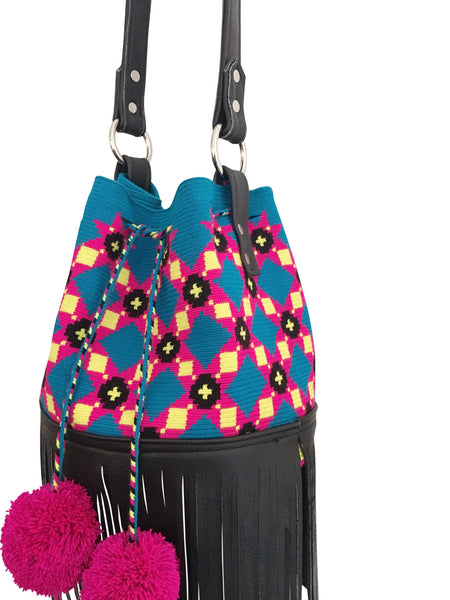 Side angle image of one strand Wayuu purse with black leather strap and fringe; bag is blue with pink, yellow black pattern and a drawstring with two pink pompoms