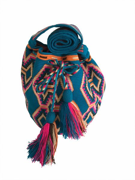 Close up image of Wayuu mochila purse, drawstring crossbody bag with tassels and cloth strap; blue base with bright pink, chocolate brown, orange, tan design