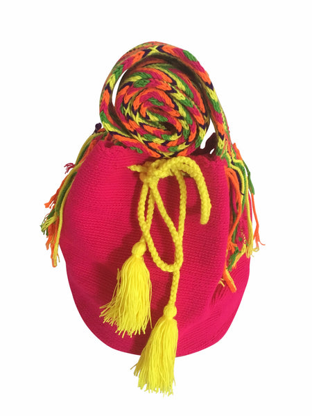 Close up image of Wayuu mochila purse, drawstring crossbody bag with tassels and cloth strap; neon pink bag with multi colored strap and neon yellow drawstring