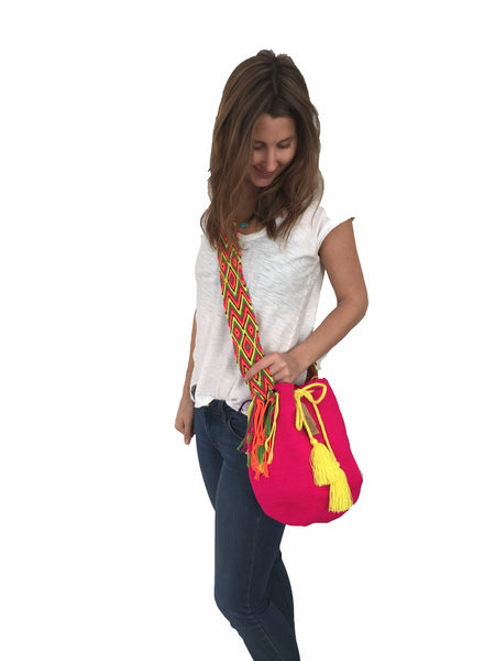 On body image of Wayuu mochila purse, drawstring crossbody bag with tassels and cloth strap; neon pink bag with multi colored strap and neon yellow drawstring