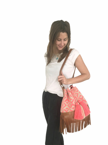 On body image of Wayuu bucket bag purse with brown leather strap and fringe; bag is tan with coral pink design