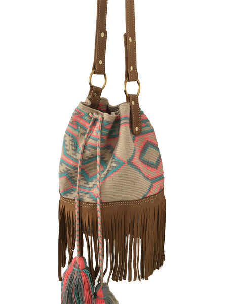 Side angle image of Wayuu bucket bag purse with brown leather strap and fringe; bag is tan with soft blue, gray and pink