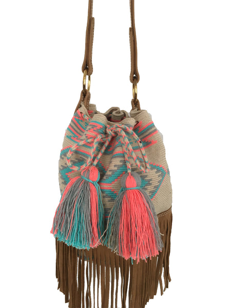 Close up image of Wayuu bucket bag purse with brown leather strap and fringe; bag is tan with soft blue, gray and pink