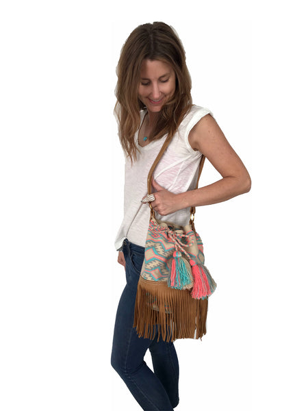 On body image of Wayuu bucket bag purse with brown leather strap and fringe; bag is tan with soft blue, gray and pink